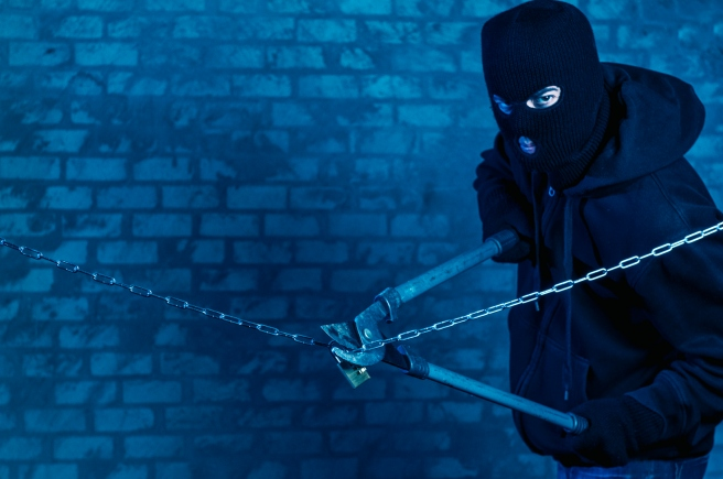 Masked man use a tool to cut a metal chain and lock.